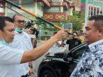 Plt Sekretaris DPRD Riau, Muflihun (kiri) mengecek suhu tubuh salah satu ASN